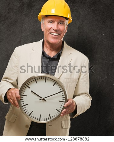Male Architect Holding Clock against a grunge background - stock photo