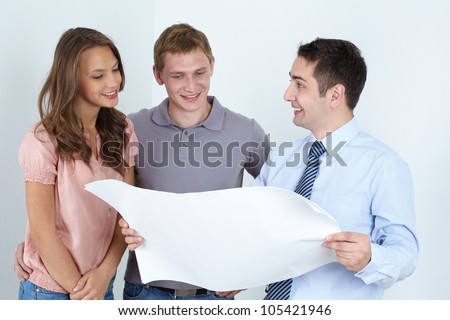 Male architect presenting the plan of the future home for the family of two - stock photo
