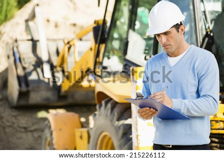 Male architect writing on clipboard against earthmover at construction site - stock photo