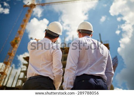 Male architects in helmets discussing new construction while standing in front of it - stock photo