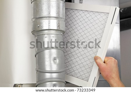 Male arm and hand replacing disposable air filter in residential air furnace. - stock photo