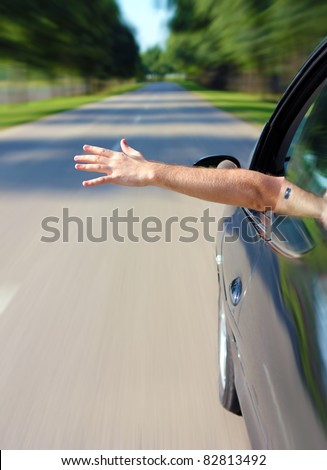 Male arm sticking out of the car - stock photo