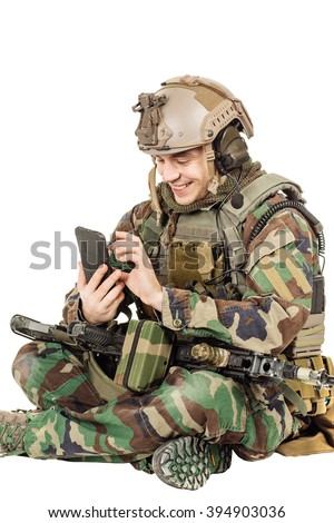 male Army soldier wearing camouflage on his mobile cell phone. - stock photo