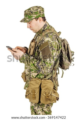 male Army soldier wearing multicam camouflage on his mobile cell phone. - stock photo
