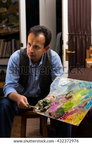 Male artist holding a colorful artists palette  and paintbrush in his hand in a gallery - stock photo