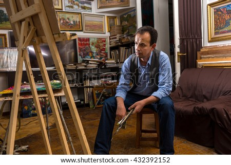 Male artist looking at his picture in his studio  paintbrush in his hand and a rag - stock photo