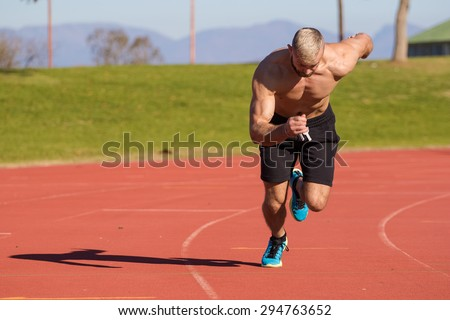 Male Athelete sprinting on a tartan athletics track on a bright sunny day - stock photo