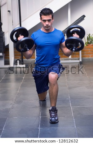 Male athelete / weightlifter, looking straight into camera, doing lunges with dumbbell weights in his hands. - stock photo