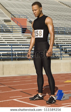 Male athlete at starting block in stadium - stock photo