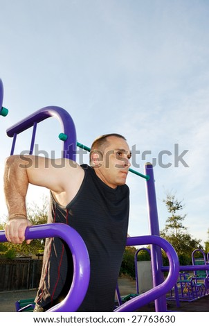 Male athlete doing dips outdoors with blue sky and white clouds in the background.