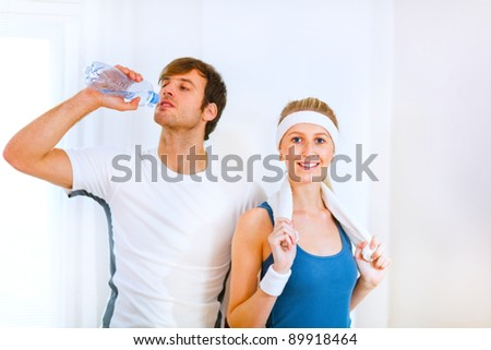 Male athlete drinking water from bottle and smiling girl in sportswear with towel - stock photo
