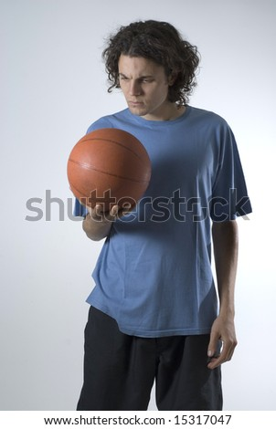 Male athlete holding a basketball and looking at the ball.  Vertically framed shot. - stock photo