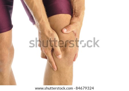 Male athlete in pain clutches his knee - stock photo