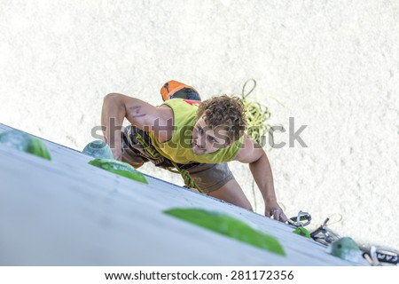 Male athlete makes hard move on climbing wall. National Climbing Championship, Lead climbing qualification round. Dnepropetrovsk, Ukraine, May 22, 2015