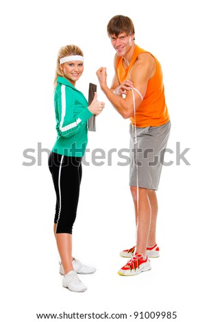 Male athlete measuring biceps and smiling girl in sportswear showing thumbs up - stock photo
