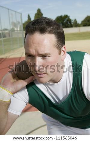 Male athlete ready to throw shot put - stock photo