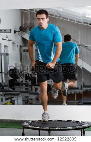 Male athlete running a trampoline. - stock photo