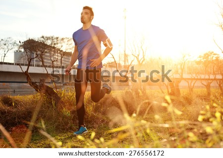 Male athlete running in the park at sunset (little motion blur, intentional sun glare) - stock photo