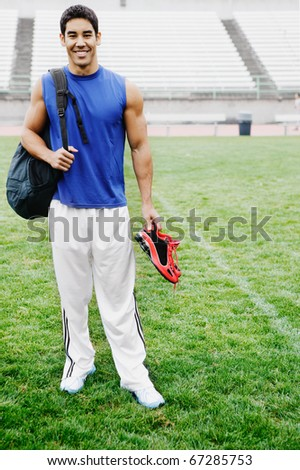 Male athlete smiling for the camera in football field - stock photo