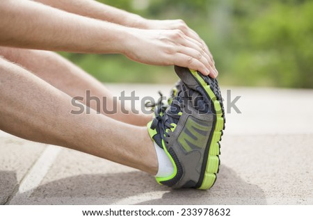 Male athlete stretching his legs and feet. - stock photo
