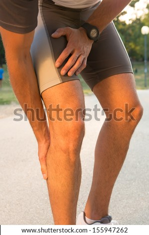 Male Athlete Suffering From Pain In Leg While Exercising  - stock photo