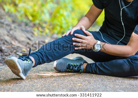 Male athlete suffering from pain in leg while exercising outdoors - stock photo