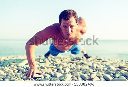 male athlete trains pushed on the nature on the beach - stock photo