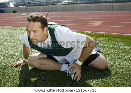 Male athlete warming up and stretching on grass - stock photo