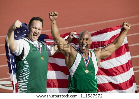 Male athlete with medal and American flag on track and field - stock photo