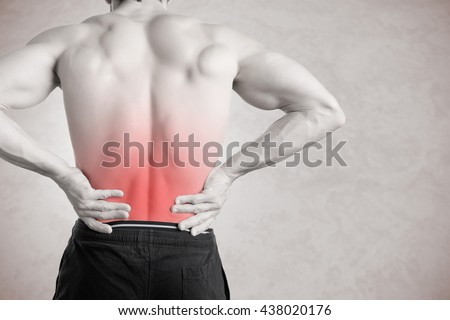 Male athlete with pain in his lower back, isolated in grey. Red spot around painful area.