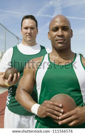 Male athletes holding shot put and discus - stock photo