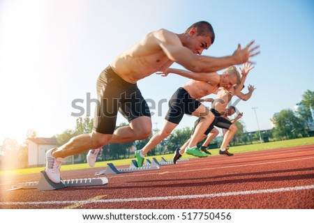 Male athletics runners on starting line without shirts.