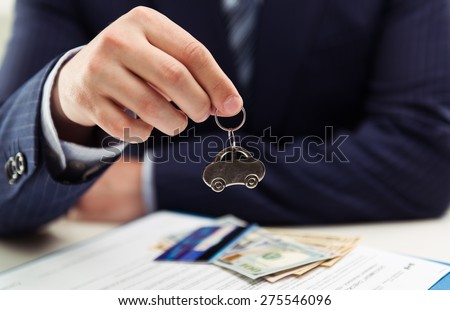 Male auto dealer selling car to client. Concept of leasing, investment and sale. Shallow depth of field. - stock photo