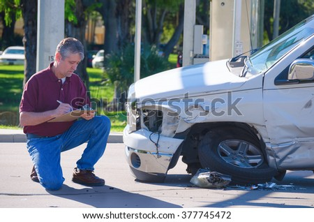 Male auto insurance adjuster inspecting a vehicle that has been in an accident wreck - stock photo