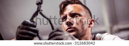 Male automotive technician working in repair shop