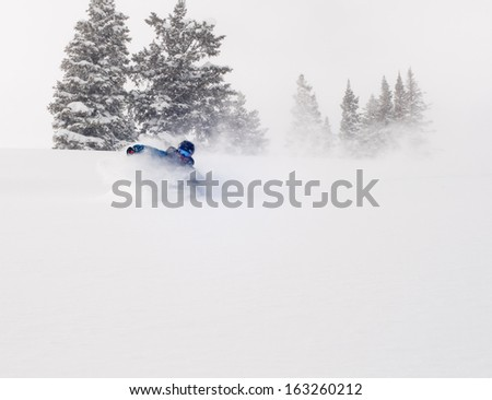 Male back-country free-rider in deep powder snow setting up for a turn