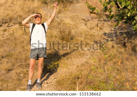 Male backpacker standing waving on a mountains slope with a broad smile to show his enjoyment of hiking in nature in the summer sunshine - stock photo