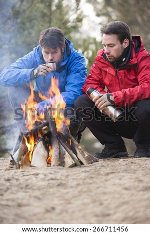 Male backpackers having coffee at campfire in forest - stock photo