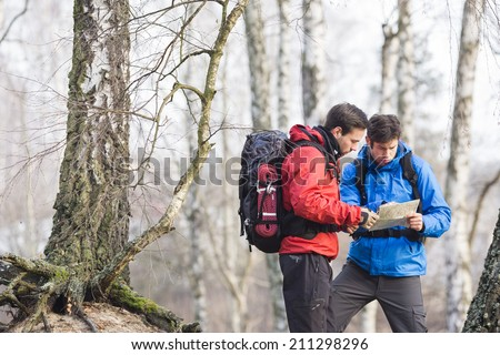 Male backpackers reading map in forest - stock photo