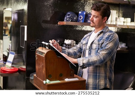 Male Barber Standing By Cash Register Writing Down Booking - stock photo