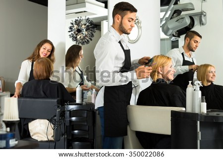 Male barber with scissors in his hands is making a haircut for a woman sitting on a chair in a salon - stock photo
