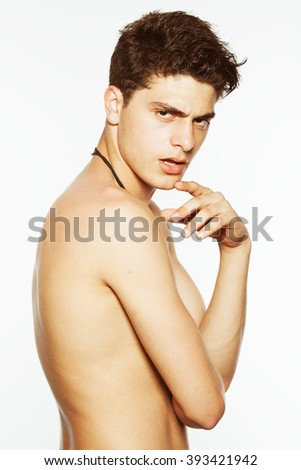 Male beauty concept. Handsome muscular male model with ethnic necklaces posing with hand on shoulder over white background. Perfect glossy wet curly hair and healthy clean skin. Fashion studio shot - stock photo