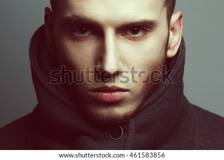 Male beauty concept. Portrait of brutal young man with short hair wearing gray sweatshirt with high collar and buttons posing over gray background. Modern street style. Close up. Studio shot