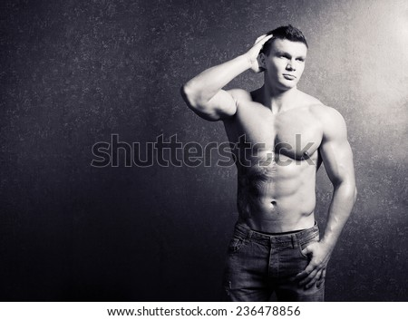 Male beauty concept. Portrait of fashionable and undressed young man in blue jeans with stylish haircut posing over gold background. Perfect hair & skin. Tough guy. Close up.  Tattoo.  Black and white