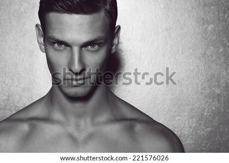 Male beauty concept. Portrait of fashionable and undressed young man with stylish haircut posing over gray background. Perfect hair & skin. Tough guy. Vogue style. Close up. Studio shot - stock photo