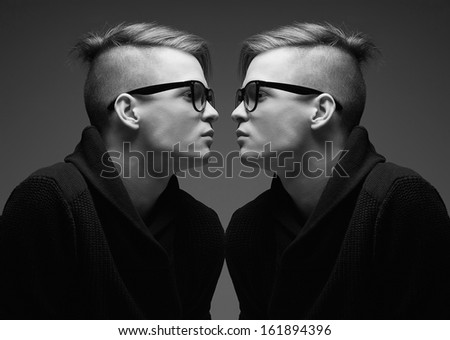 Male beauty concept. Portrait of fashionable young twins with stylish haircut wearing trendy glasses and sweater posing over gray background. Perfect hair & skin. Hipster style. Close up. Studio shot - stock photo