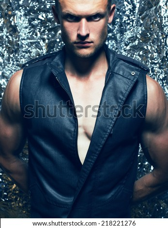 Male beauty concept. Portrait of handsome muscular male model in dark jeans west posing over foil background. Healthy clean skin. Close up. Fashion studio shot - stock photo
