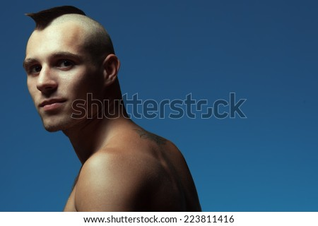 Male beauty concept. Portrait of handsome muscular male model posing over blue background. Shaved head with upright crest. Healthy skin, hairy chest. Tough guy style. Copy-space. Close up. Studio shot - stock photo