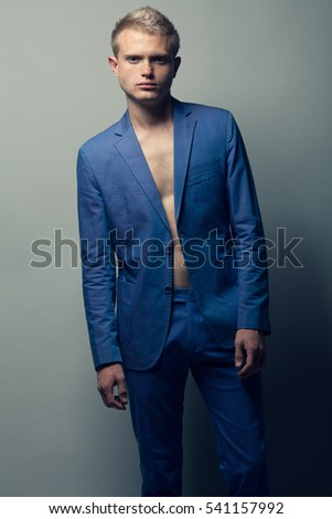 Male beauty concept. Portrait of young man with perfect haircut wearing blue classic jacket. Hollywood star style. Blue-eyed boy with blond hair. Studio shot