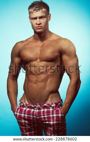 Male beauty & fashion concept. Portrait of handsome muscular male model in trendy summer pants posing over blue background. Blond hair and healthy clean skin. Studio shot - stock photo
